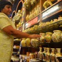 A Delhi woman inspects some hand painted vases.