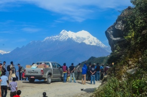 With Mt. Langtang towering in the background, weary passengers filed off buses and other vehicles to investigate the cause for a traffic jam.