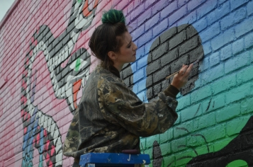 Local artist Shaina Kasztelan donning green hair to match her mural. (ISO 200, 55mm, f5.6, 1/640)